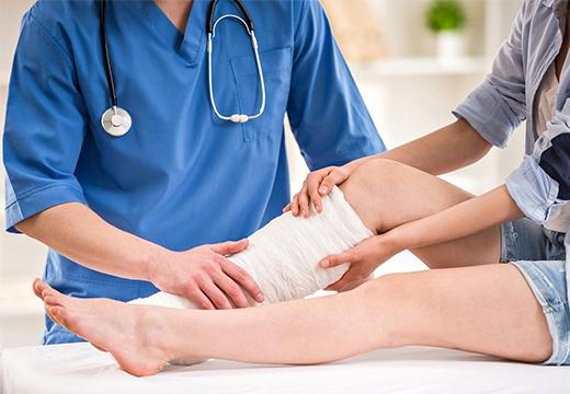 доктор касается ноги пациента